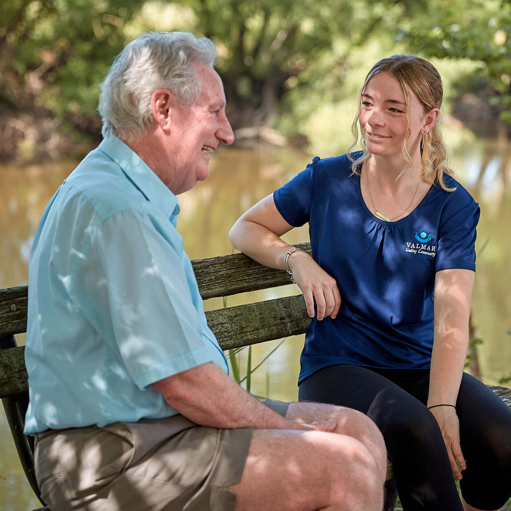 An elderly gentleman in a blue collared shirt and grey shorts sitting on a park bench. Next to him is a young woman with long blonde hair wearing a blue Valmar Support Services uniform.