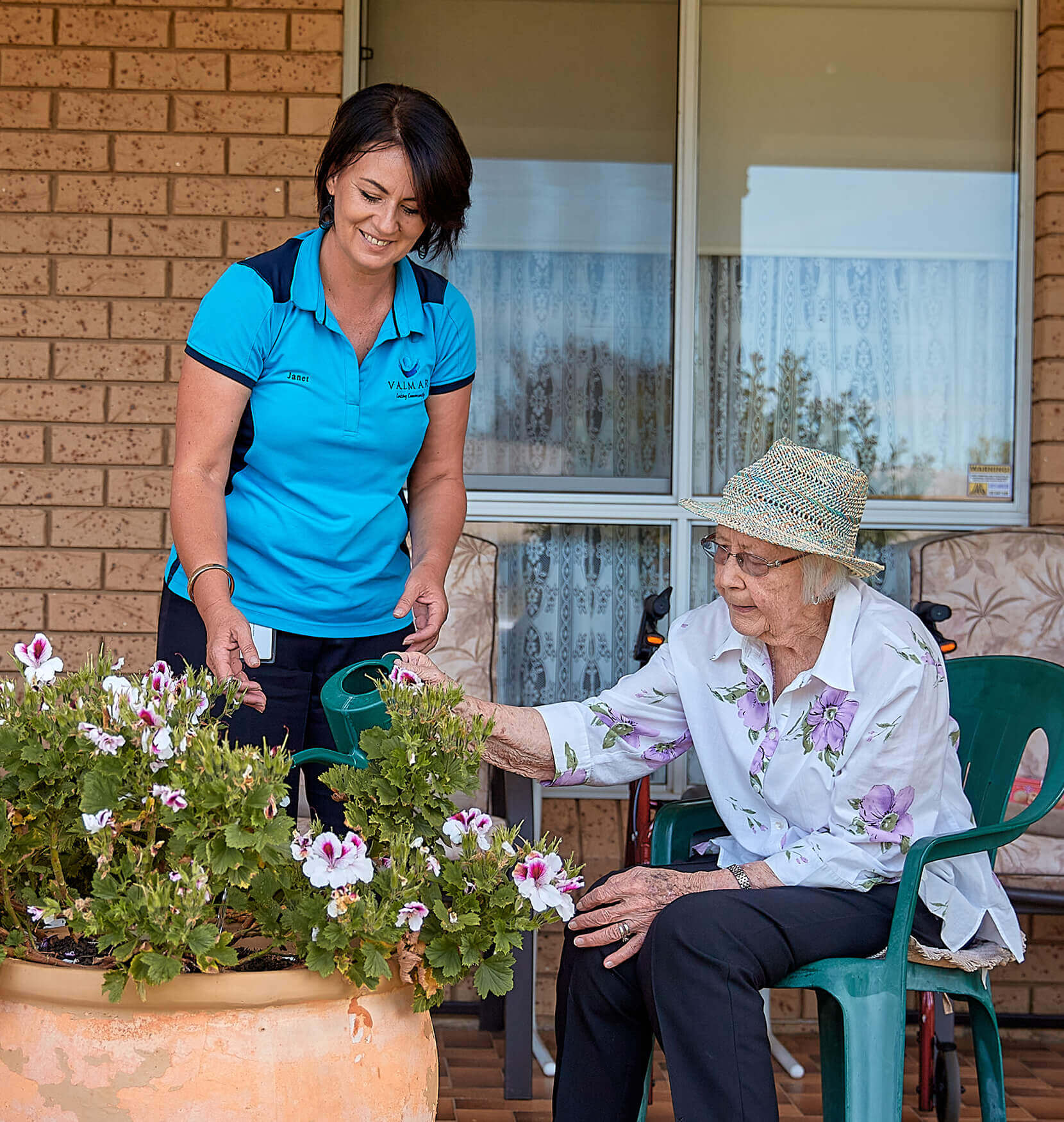 An elderly woman sitting on a green garden chair watering some purple flowers. A younger woman in a bright blue Valmar Community Aged Care uniform is smiling while overseeing the watering.