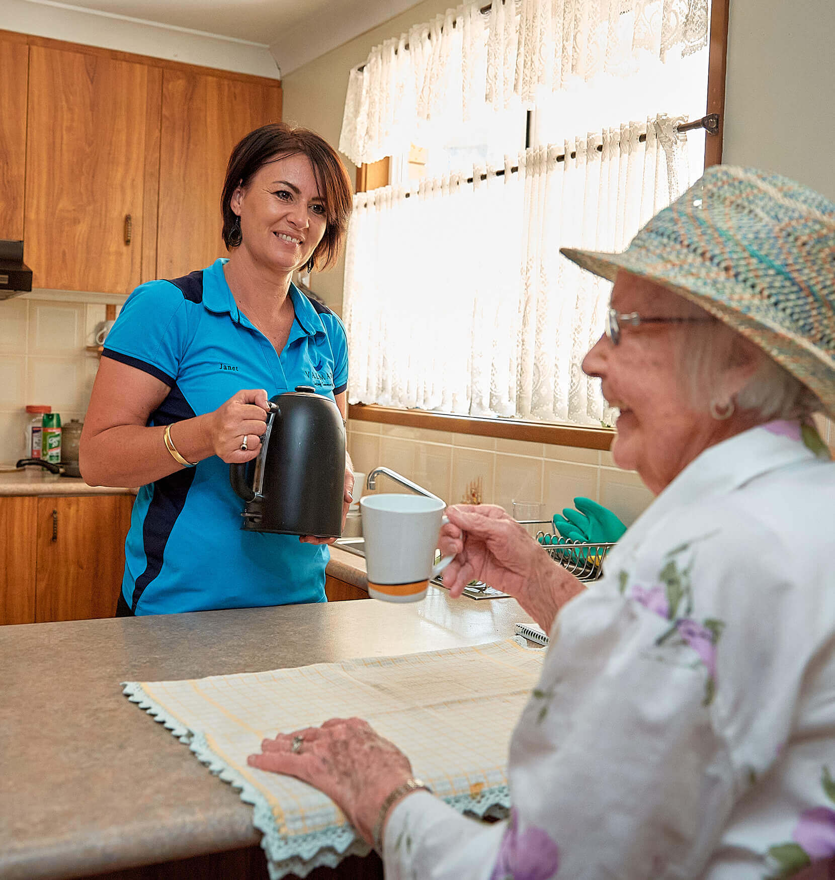 A woman in a blue Valmar Support Services uniform serving a kettle to an elderly woman who is sitting at a kitchen counter and holding out a white tea cup in her right hand.