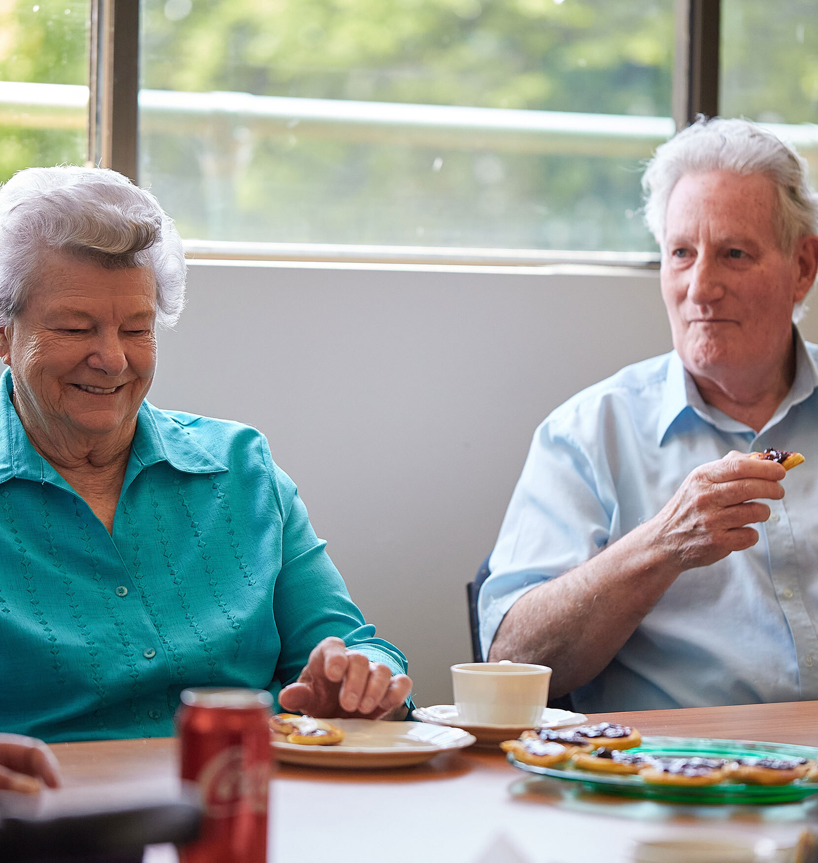 An elderly man and woman sitting at a dining table. They have a plate of biscuits in front of them and the man is holding one. They're both grinning.