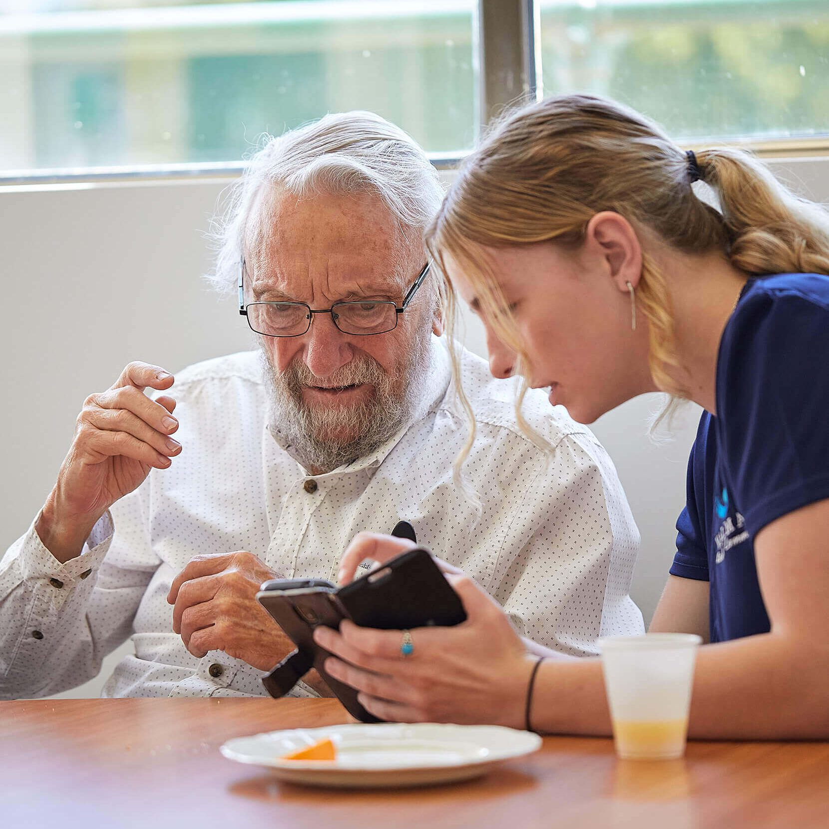 A young woman assisting an elderly gentleman to use a smartphone. They are sitting at a wooden table and an empty plate and small cup of orange juice is in front of them.