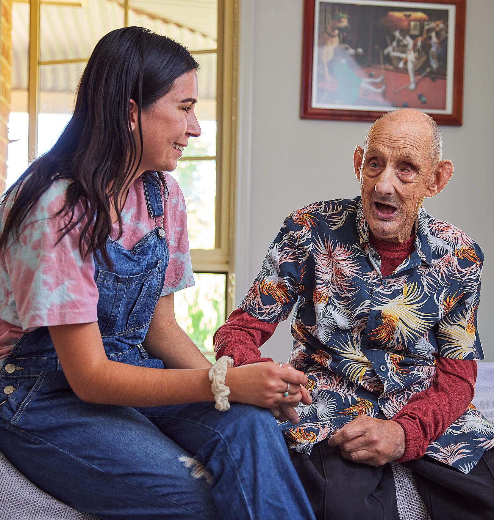 An image of an elderly man in a bright floral shirt sitting next to a young brunette woman wearing overalls. She is gently holding his hand and smiling.