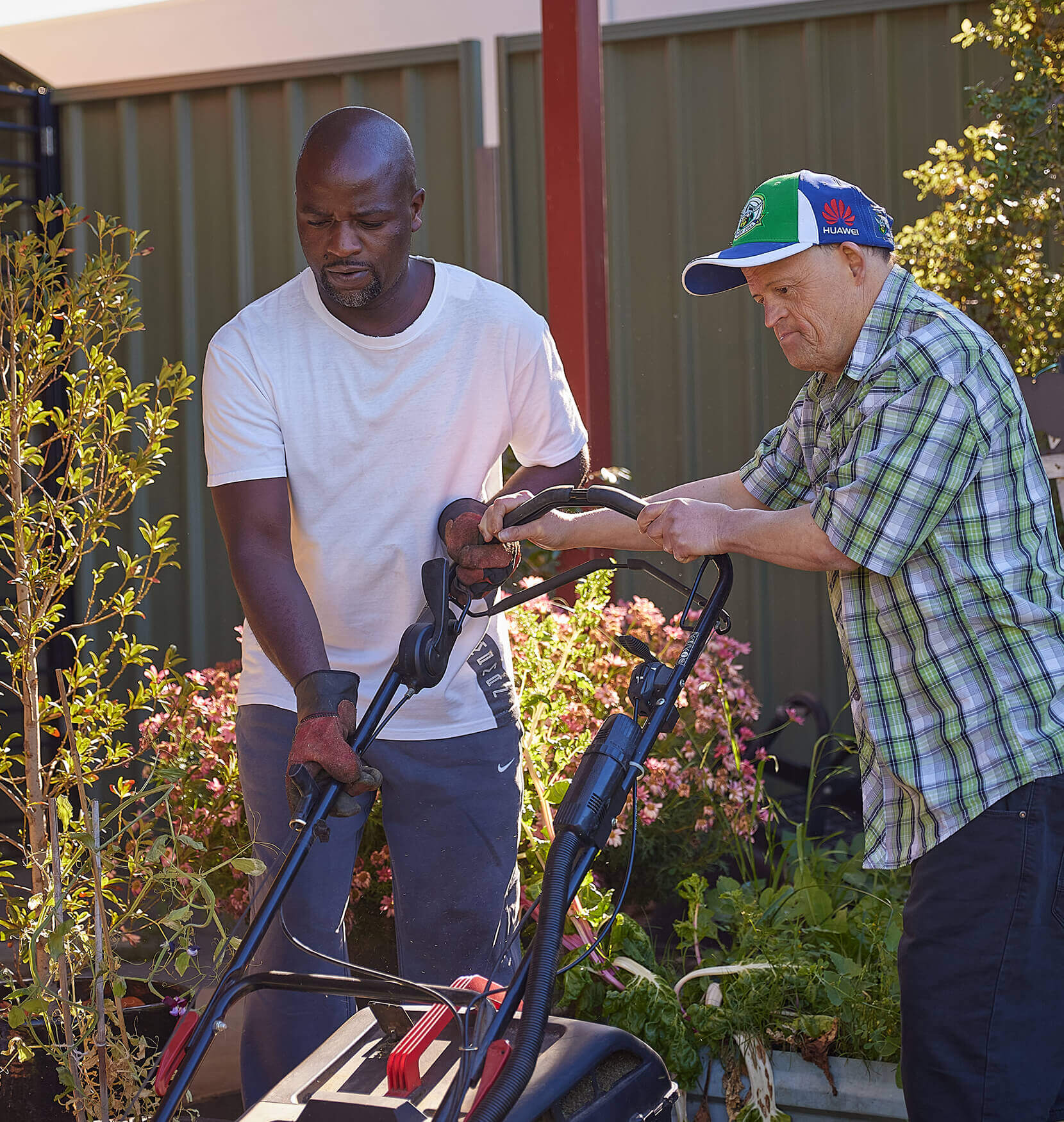 A man in a white t-shirt is helping a man in a flannel shirt and sports cap to push a lawn mower