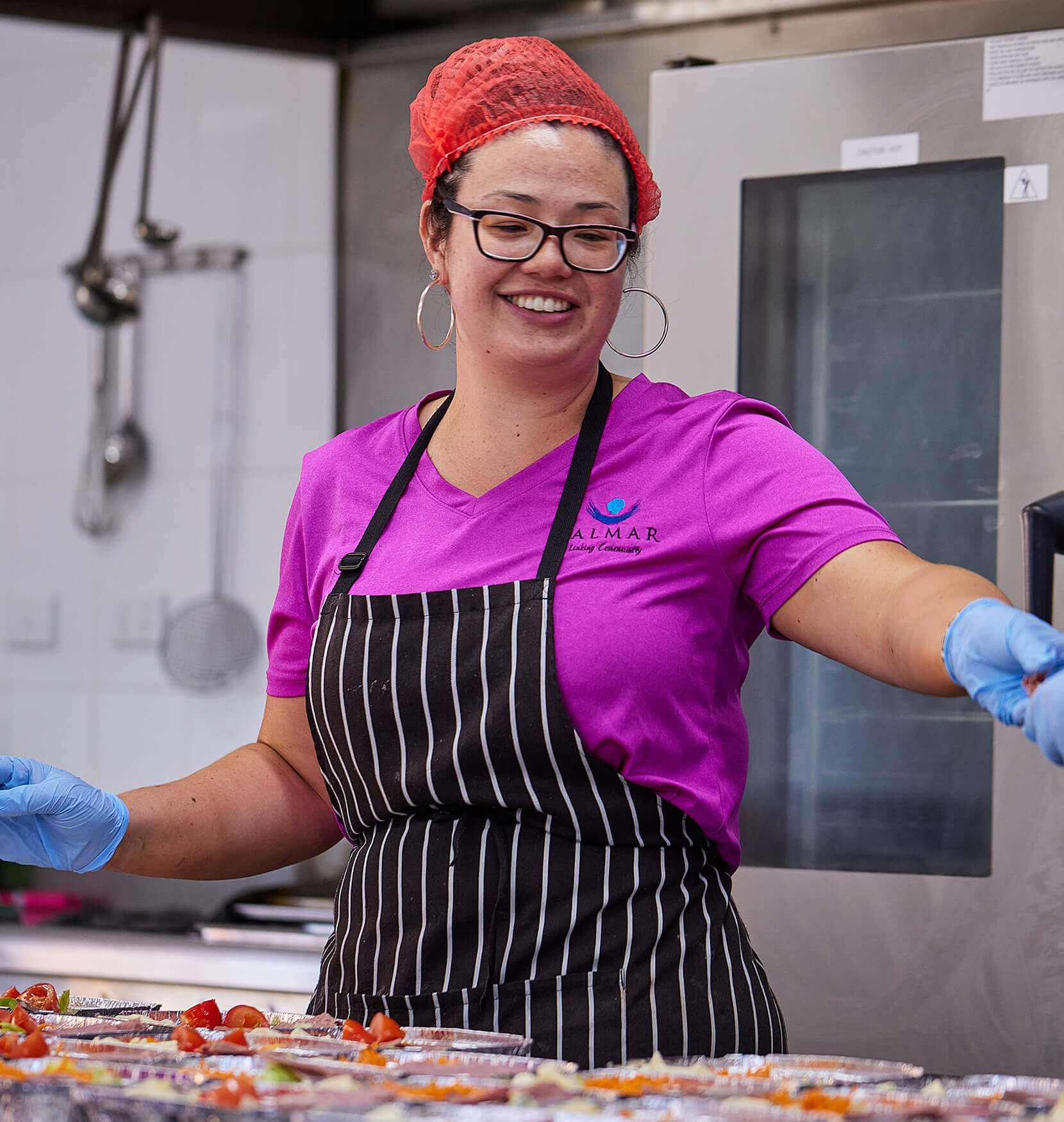 A woman working in a commercial kitchen wearing a bright pink shirt with a dark apron and blue hygienic gloves. She is smiling and her is covered by a red hair net.