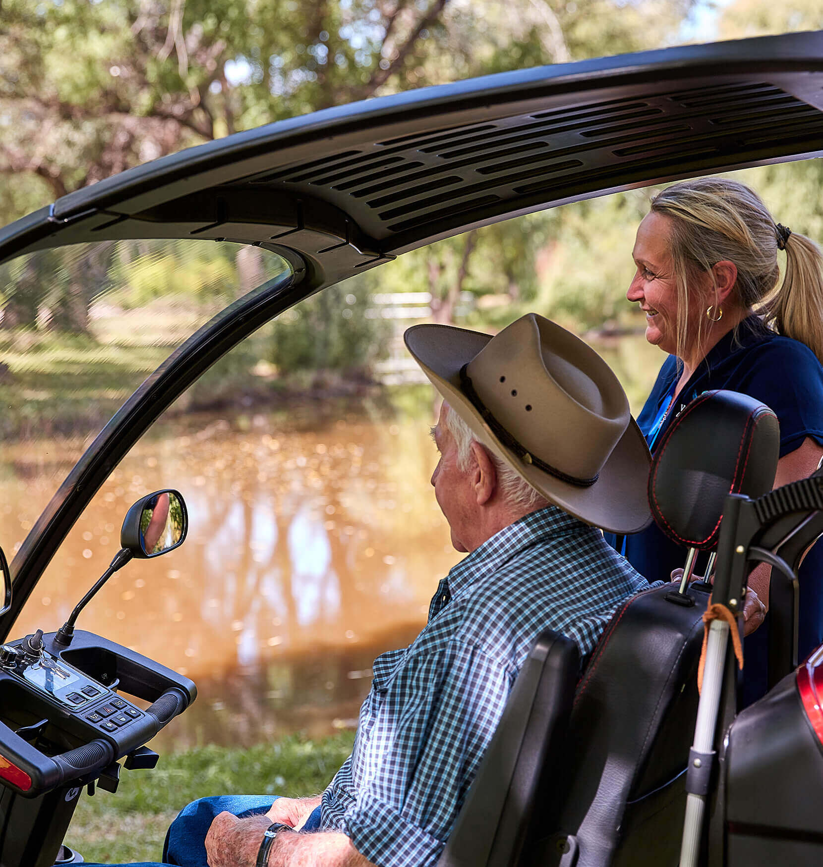 A man in a akubra hat and chequered shirt sitting in the cabin of a buggy gazing out at a muddy river. A woman is standing next to him outside the buggy smiling. She had a blonde hair in a ponytail.