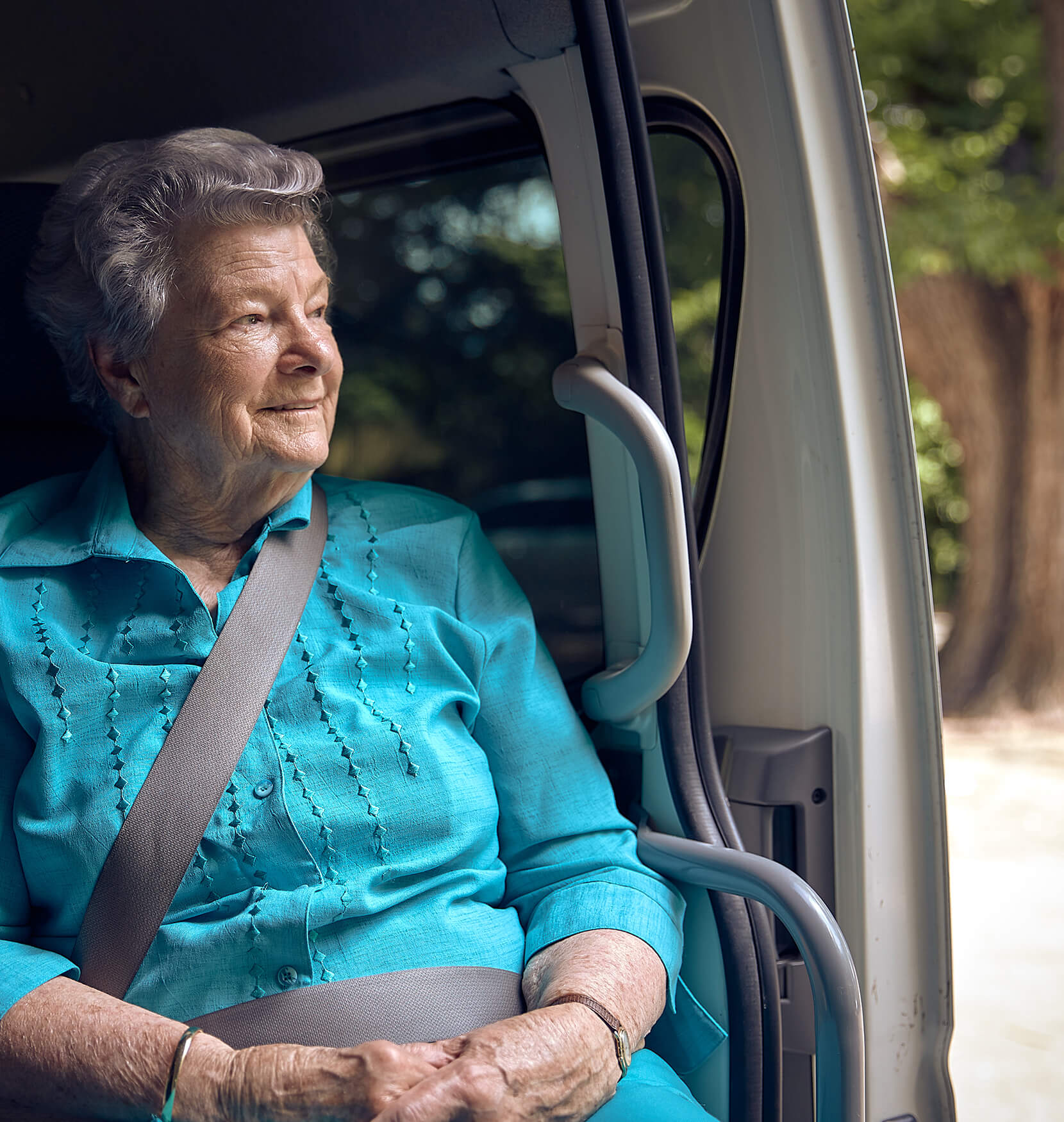 A senior woman looking out of the passenger seat of a mini van while smiling