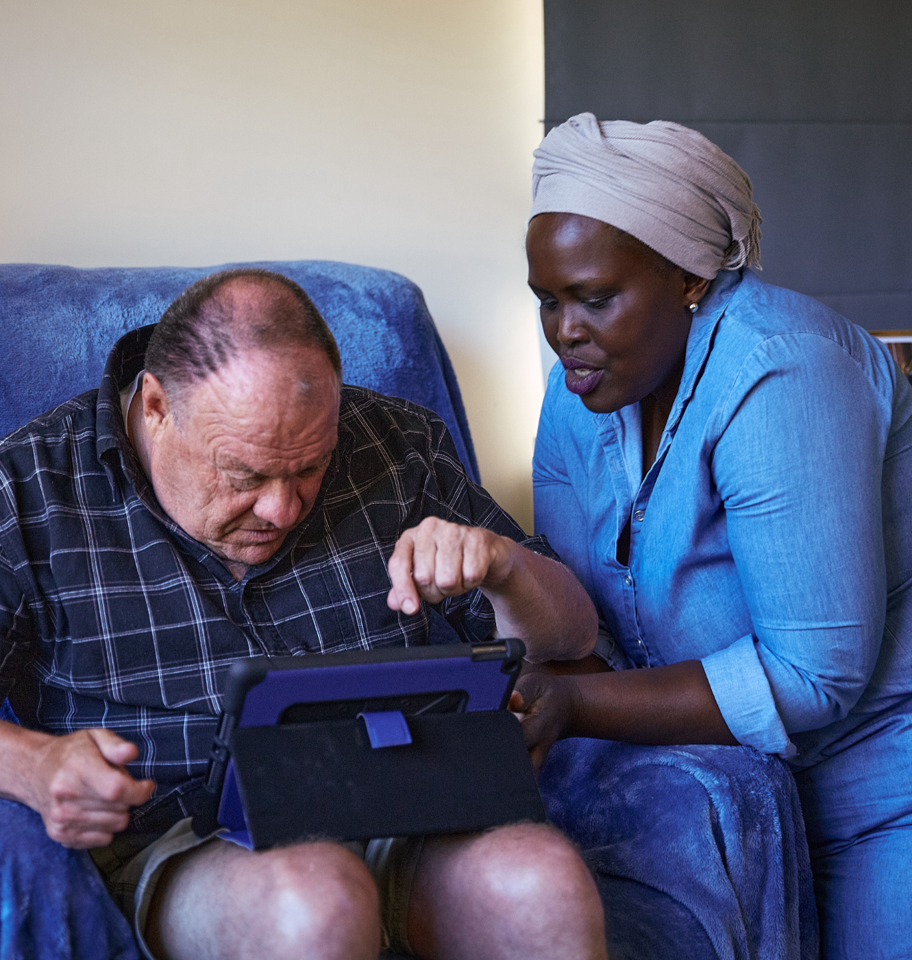 A man in a blue armchair being assisted to use an iPad by a Valmar disability support worker