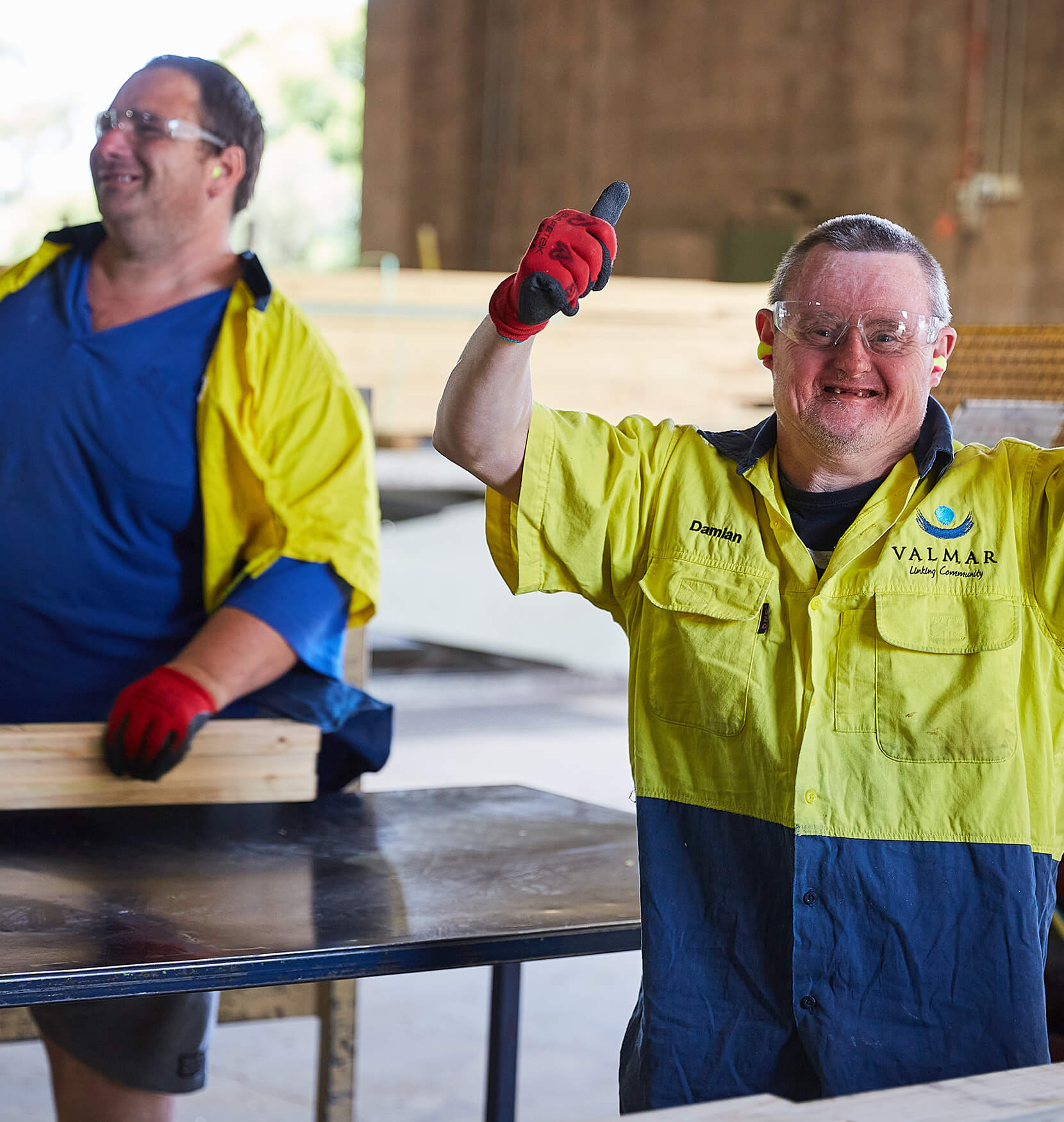 A smiling man in hi-vis work gear in a workshop holding his hands up in a cheering pose