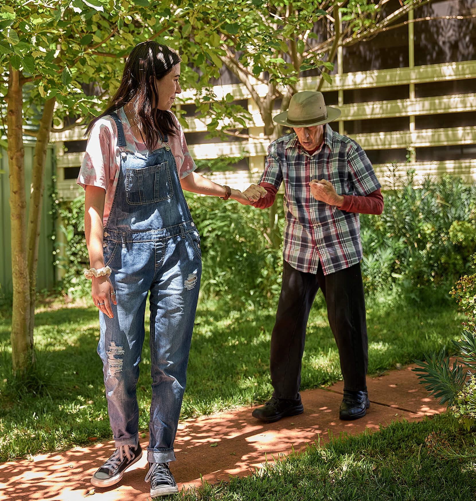 A photo of an older man in a vibrant green garden wearing a wide brimmed hat and flannel shirt. He is being assisted by a young woman in denim overalls who is holding the mans hand and gently guiding him.