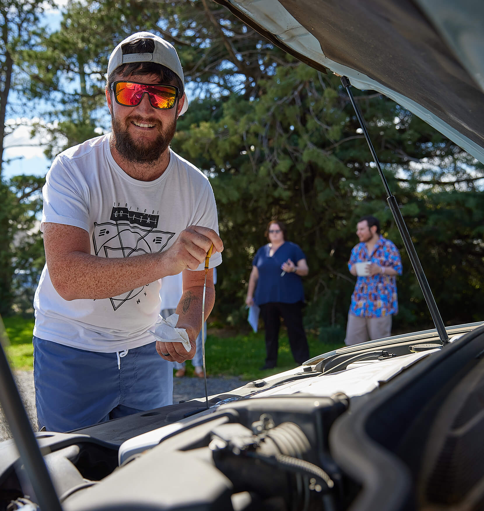 A young man with a short bears wearing polarised sunglasses and a backwards cap. He is smiling and checking the oil in a car engine.