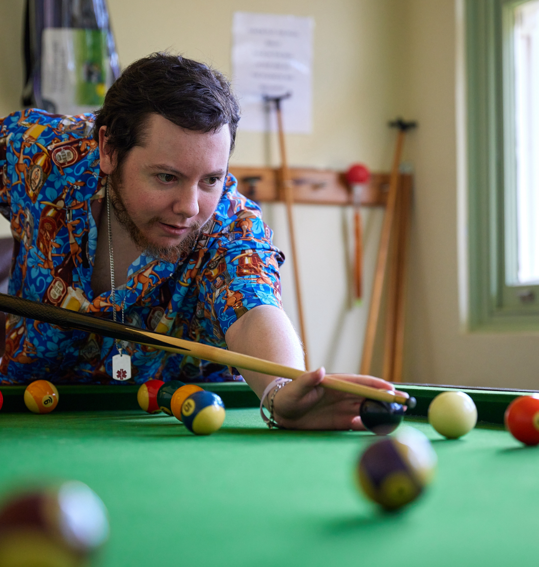 A young man in a colourful shirt lining up the cue ball in a game of snooker or pool