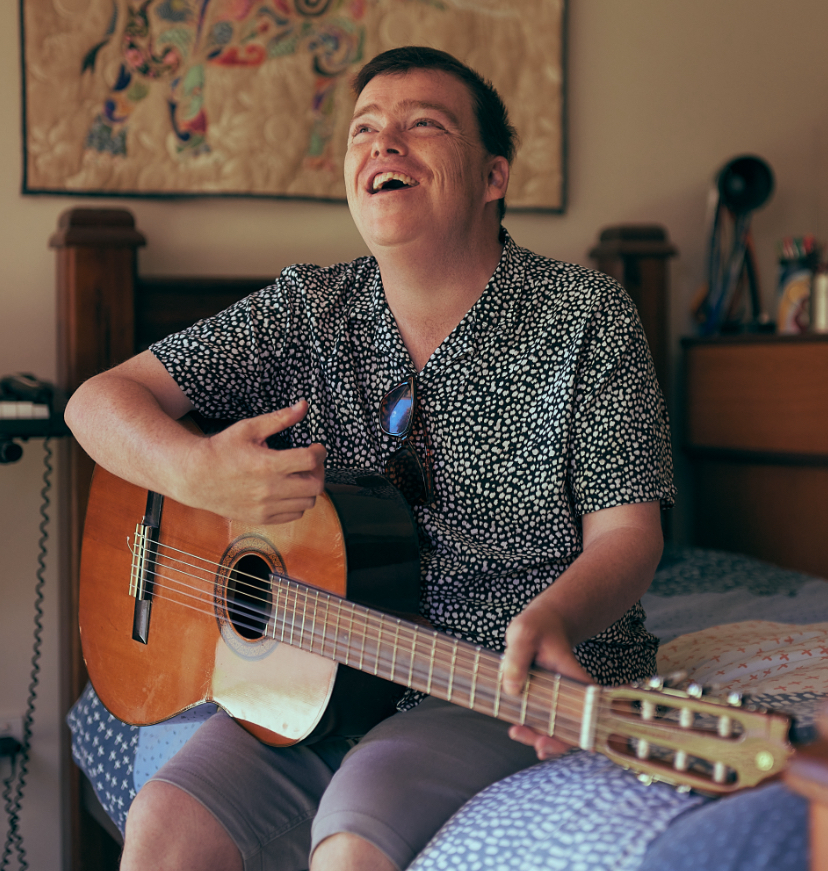 A young man in a paisley shirt sitting on his bed smiling and playing an acoustic guitar.