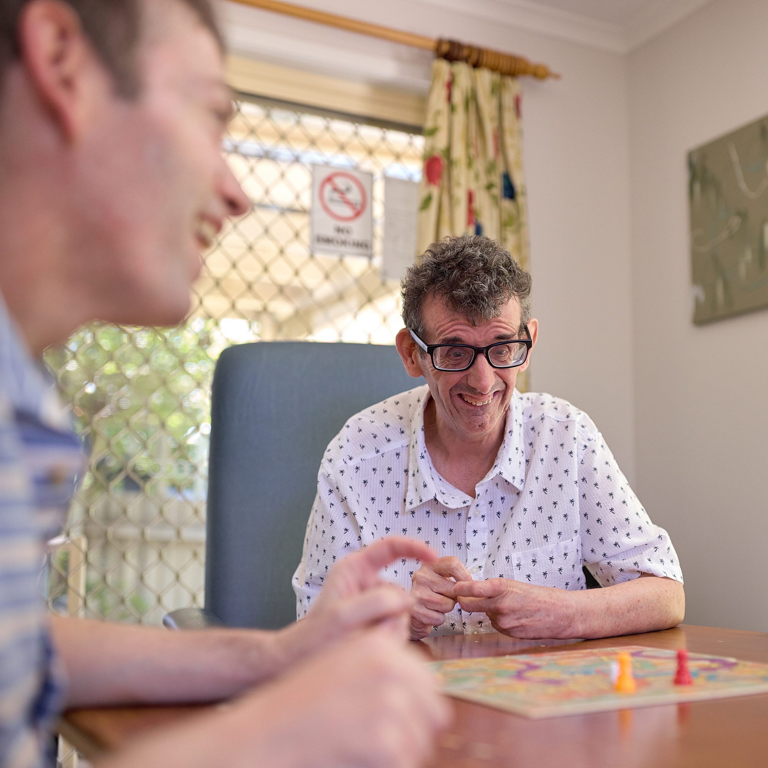 A man in a striped polo shirt playing the game of life board game
